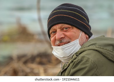Portrait on blurred marine background of mature man smiling with surgical mask and striped hat.