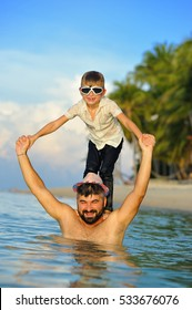 Portrait on tropical beach: 8 years old boy in wet clothes and glasses for scuba diving standing on dad's shoulders. Bearded man in fedora hat. Men both in water - wet and happy fooling around