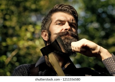 Portrait of one handsome strong stylish male logger of young serious man with long lush black beard and moustache in shirt holding wooden axe standing sunny day outdoor on natural background, vertical