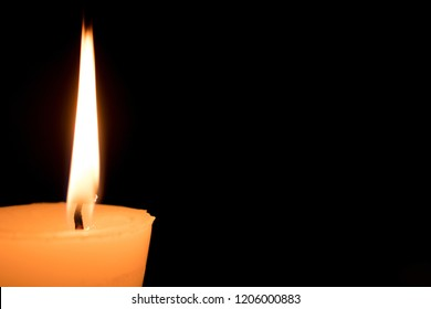 Portrait of one light candle burning brightly on black background. Close-up flame.