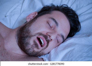 Portrait of one man sleeping in bed and snoring