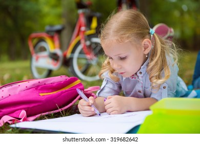 Portrait of one pretty girl, she draws in park