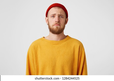 Portrait of one sad bearded man looking upset because of the girlfriend, in a bad mood, ready to cry, with hopeless facial expresion, over white wall