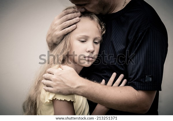 portrait of one sad daughter hugging his father