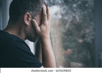 portrait one sad man standing near a window and covers his face at the day