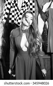 Portrait of one sexual pretty sensual diva young woman with long hair in dress with deep low neck standing in wardrobe among many colorful bright clothes black and white, vertical picture