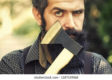 Portrait of one strong stylish male logger of young serious man with long lush black beard and moustache in shirt holding wooden axe standing sunny day outdoor on natural background, horizontal