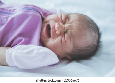 A portrait of an one week old crying baby in a blanket