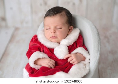 Portrait of one week old newborn baby girl sleeping in a chair and wearing a red and white Mrs. Claus dress.