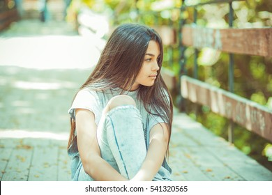 Portrait of one woman looking side wards thinking sitting on a bridge in a park outdoors background late summer.