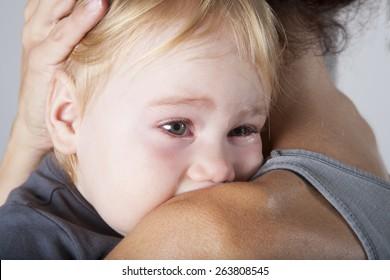 portrait of one year age blonde lovely cute caucasian white baby grey shirt looking  face crying and scream shout with tears eyes in brunette woman mother arms embrace hug