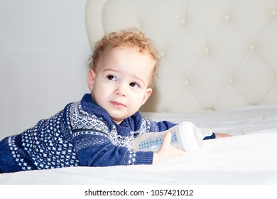 Portrait of a one year old adorable baby boy with blond curly hair.
