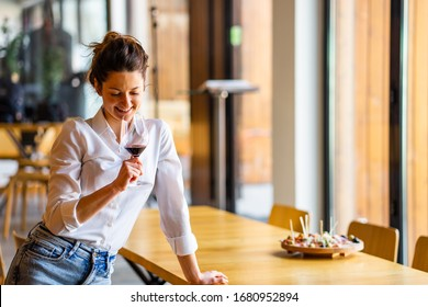 Portrait of one young beautiful caucasian woman standing by the table leaning holding and looking in glass of red wine at home alone smiling wearing white shirt front view