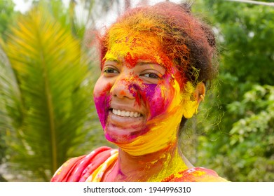 Portrait Of One Young Indian Happy woman with pink, yellow and red Holi colored powder paint on face During Holi Color festival. Front View. Looking at camera.