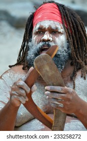 Portrait of one Yugambeh Aboriginal man holds boomerangs and sing during Aboriginal culture show in Queensland, Australia.