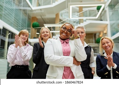 portrait of open-minded director of company and her employees clapping hands in the background, afro american smiling lady stand in the center and smile at camera, successful multi-ethnic team.