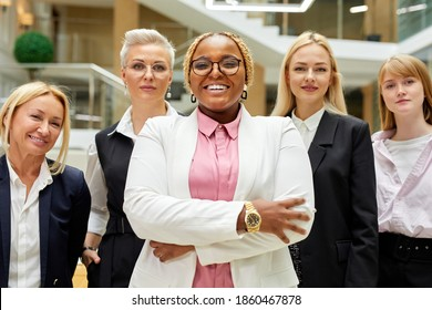portrait of open-minded director of company and her employees in the background, afro american smiling lady stand in the center and smile at camera, successful multi-ethnic team