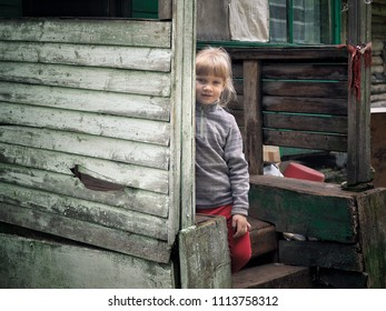 Portrait oPortrait of a village little girl. The porch of the old housef a village little girl. The porch of the old house