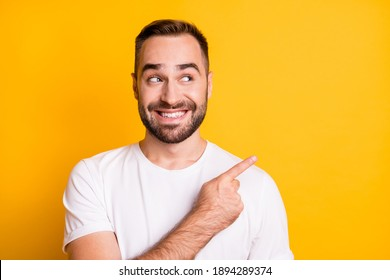 Portrait of optimistic guy point look empty space wear white t-shirt isolated on vibrant yellow color background