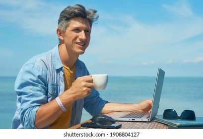 Portrait optimistic smiling man freelancer working outdoors on beach by blue sea, drinking coffee, using laptop computer. Dream office job workplace.