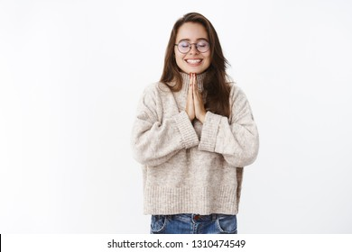 Portrait of optimsitic lucky and dreamy girlfriend in glasses and sweater close eyes as holding hands in pray near chest smiling broadly, delighted hoping dream come true, making wish over gray wall