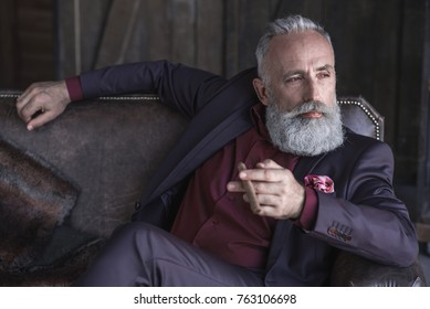Portrait of orderly bearded old businessman keeping tobacco while relaxing on comfortable couch. Leisure concept