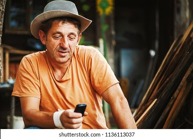 Portrait of an ordinary country man in Serbia, working and communicating with mobile.