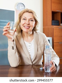 Portrait of ordinary mature woman with clean water at table