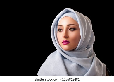 portrait of an oriental girl with a scarf ha head. arab woman close-up. Black background - Image