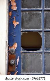 Portrait orientation close up of broken window pane in an old door with peeling paint.