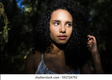 portrait outdoors of a young afro american woman. Black background. Lifestyle. Casual clothing