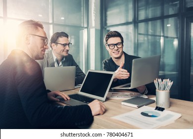 Portrait of outgoing young male showing information on laptop to colleagues. They sitting at table in room. Conference concept