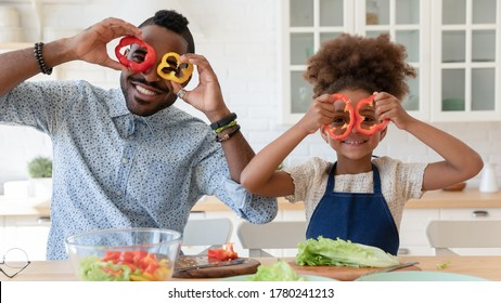 Portrait of overjoyed african american young dad and little daughter make funny faces with vegetable cooking together, happy biracial father and small girl child have fun preparing food in kitchen