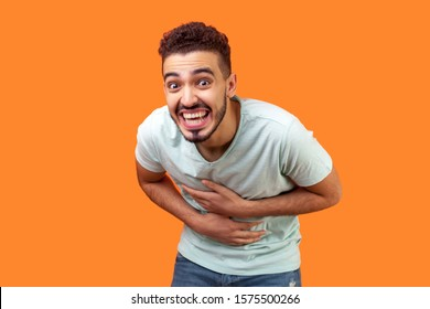 Portrait of overjoyed, extremely happy brunette man with beard in white t-shirt hunching from laughter, holding his belly and laughing out loud, crazy face. studio shot isolated on orange background