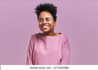 Portrait of overjoyed happiness African American female, widely smiled and close eyes, celebrates her success, poses against lavender background. People, happiness, success concept.