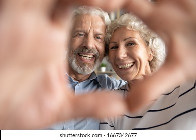Portrait of overjoyed middle-aged 60s retired couple look at camera make heart with hands posing, smiling elderly 50s husband and wife have fun show love and care, elderly relationships concept