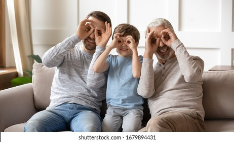 Portrait of overjoyed three generations of men sit on couch posing for funny picture together, smiling little boy with young dad and senior grandfather make face gestures look at camera at home