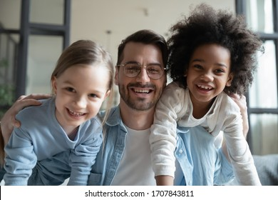 Portrait of overjoyed young Caucasian father have fun with excited little multiracial daughters at home, happy dad play engaged in funny activity with small multiethnic children on family weekend