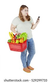 Portrait of overweight woman looking on smartphone while carrying vegetables and fruits on shopping cart, isolated on white background