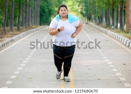 Portrait of overweight woman wearing sportswear while doing runs exercise on the road