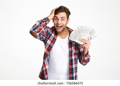 Portrait of a overwhelmed excited man holding bunch of money banknotes and looking at camera isolated over white background