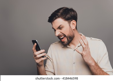 Portrait of overworked sad businessman holding phone and yelling