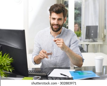 Portrait of overworked young businessman takes the medicine while sitting at workplace in front of computer.