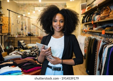 Portrait of the owner of a clothing store at the entrance of the new business with the tablet in hand to analyze the sales, new orders to be sent and check the stocks