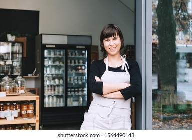 Portrait of owner of sustainable small local business. Shopkeeper of zero waste shop standing on interior background of shop. Smiling young woman in apron welcoming at entrance of plastic free store