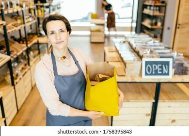 Porträt des Eigentümers der nachhaltigen kleinen lokalen Unternehmen. Shopkeeper von Null-Müll-Shop steht auf dem inneren Hintergrund des Ladens.Junge Frau in Schürze hält Papier-Tasche aus Kunststoff-freien Speicher.