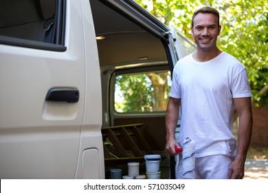 Portrait of painter holding paint roller standing near his van