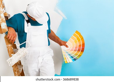 portrait of painter man with paint roller and wooden vintage ladder showing a color palette, on half painted wall
