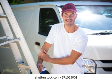 Portrait of painter with stepladder and bucket standing near his van
