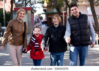 Portrait parents with children posing outdoor in cold day and smiling
